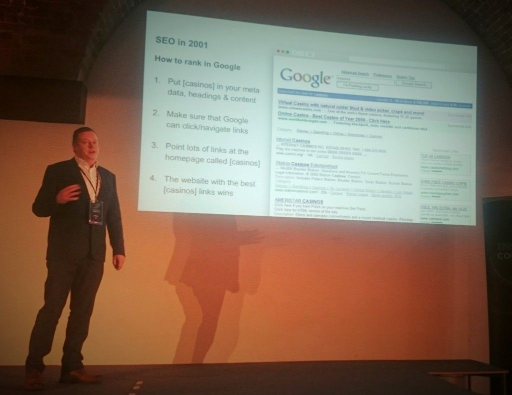 "Rob Kerry stands next to a projection screen at Ayima Insights conference. The projector reads 'SEO in 2001: How to rank in Google' with a set of numbered instructions below for SEO optimising a casino website. 1. Put ""casinos"" in your meta data, headings and content. 2. Make sure that Google can click/navigate links. 3. Point lots of links at the homepage called ""casinos"". 4. The website with the best ""casinos"" links wins. To the right there is a screenshot of 2001-style Google search results for the word ""casinos""."